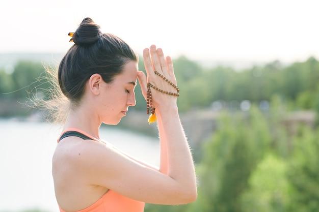 Giovane donna concentrata con chignon per capelli che tiene perline di mala mentre si esegue la pratica spirituale all'aperto