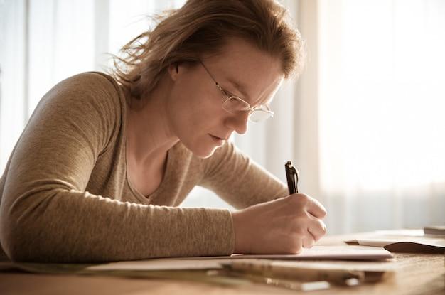 Giovane donna concentrata sulla scrittura di compiti mentre studiava a casa