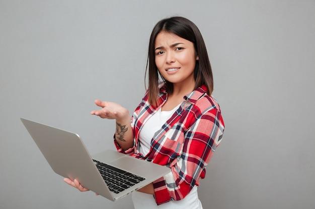 Giovane donna confusa che per mezzo del computer portatile.