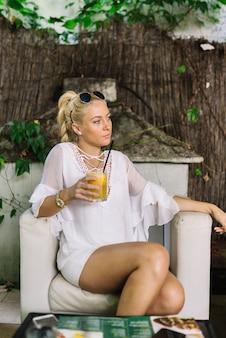 Giovane donna contemplata che si siede nella sedia bianca che tiene vetro di succo