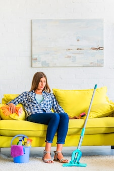 Giovane donna contemplata che si siede sul sofà con le attrezzature di pulizia a casa