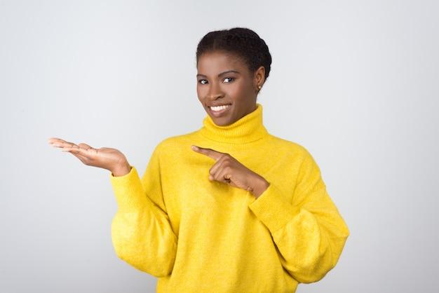 Giovane donna contenta che mostra lo spazio della copia