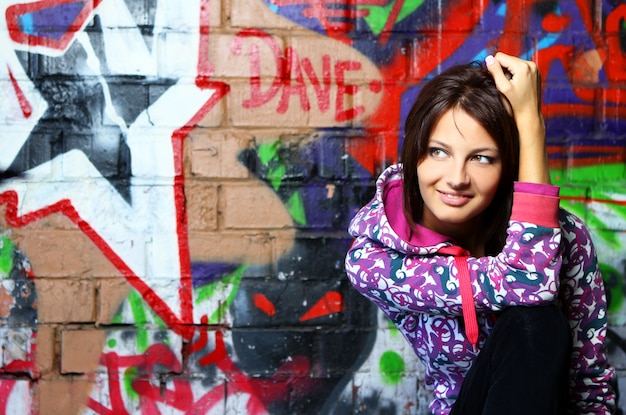 Giovane donna contro il muro con i graffiti