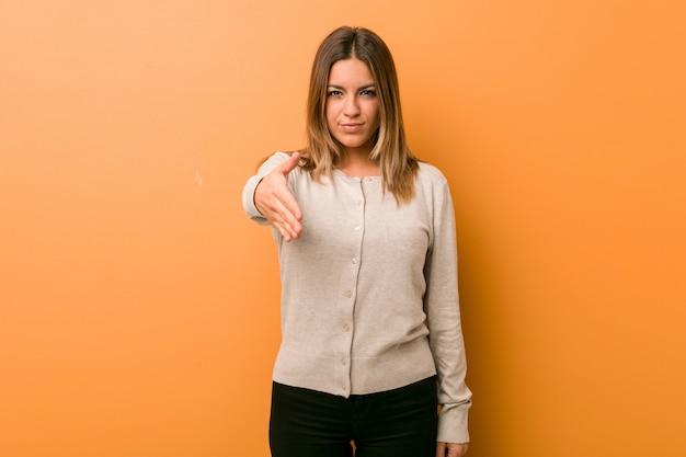 Giovane donna contro una parete che allunga mano alla macchina fotografica nel gesto di saluto.