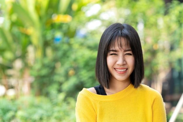 Giovane donna creativa asiatica attraente del progettista che sta, sorridendo, esaminante la sensibilità della macchina fotografica felice.