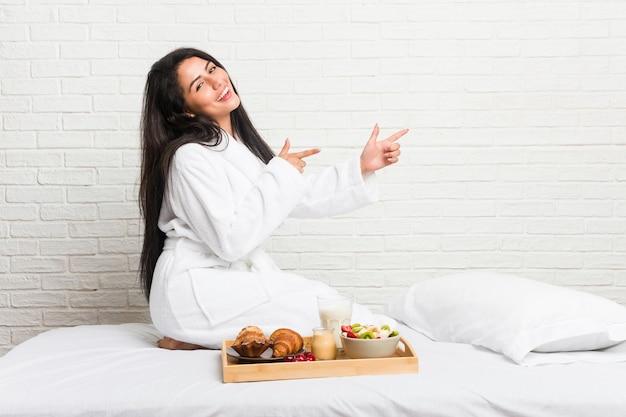 Giovane donna curvy che fa colazione sul letto eccitata indicando con gli indici di distanza.