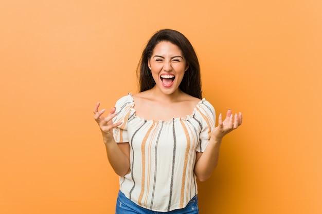 Giovane donna curvy che grida con rabbia.
