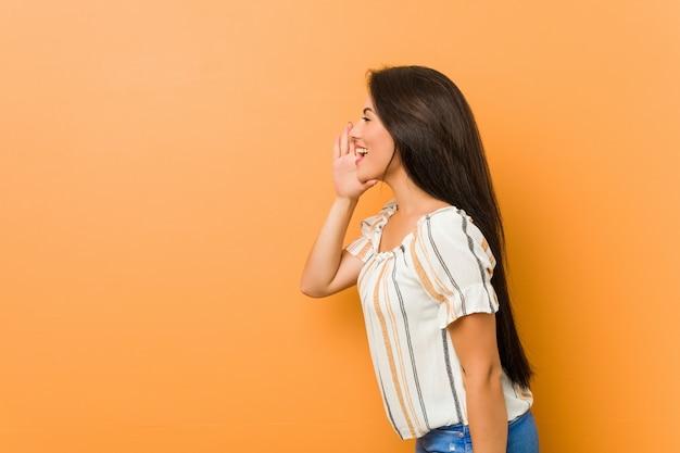 Giovane donna curvy che grida e che tiene la bocca aperta vicina della palma.