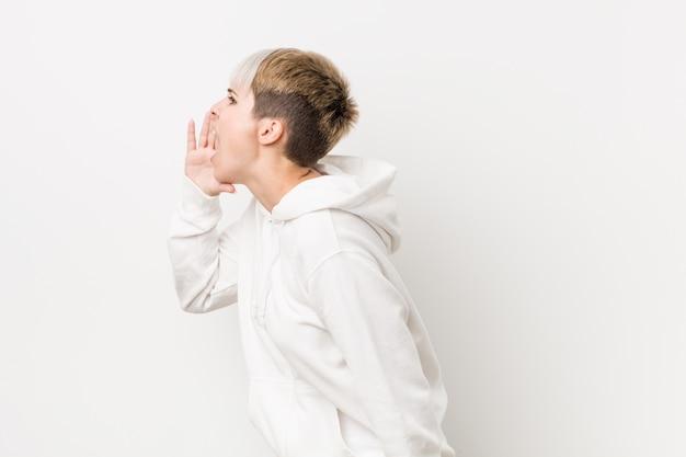 Giovane donna curvy che indossa una felpa con cappuccio bianca che grida e che tiene la bocca aperta vicino della palma.