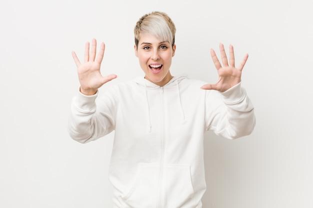 Giovane donna curvy che indossa una felpa con cappuccio bianca che mostra numero dieci con le mani.