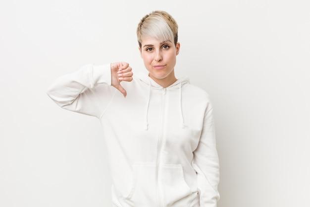 Giovane donna curvy che indossa una felpa con cappuccio bianca che mostra un gesto di avversione, pollice in giù. concetto di disaccordo