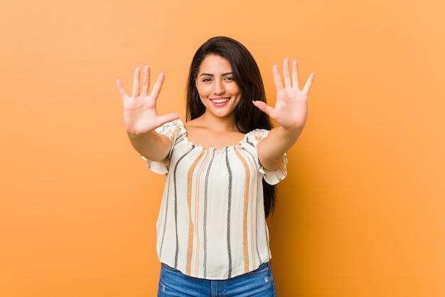 Giovane donna curvy che mostra numero dieci con le mani.