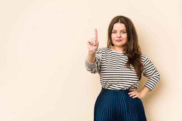 Giovane donna curvy che mostra numero uno con il dito.