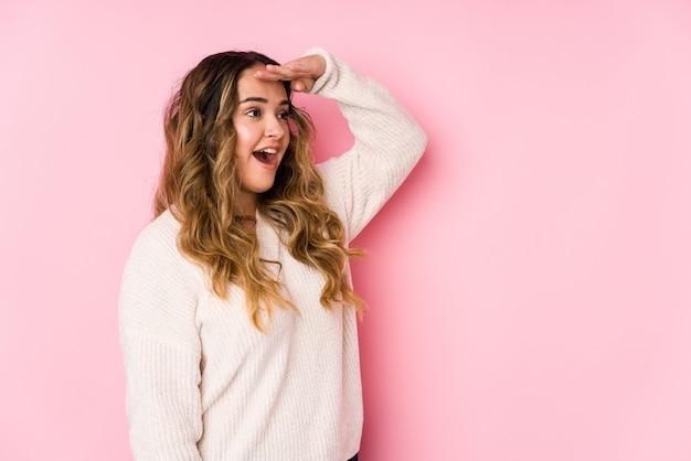 Giovane donna curvy che posa nel rosa