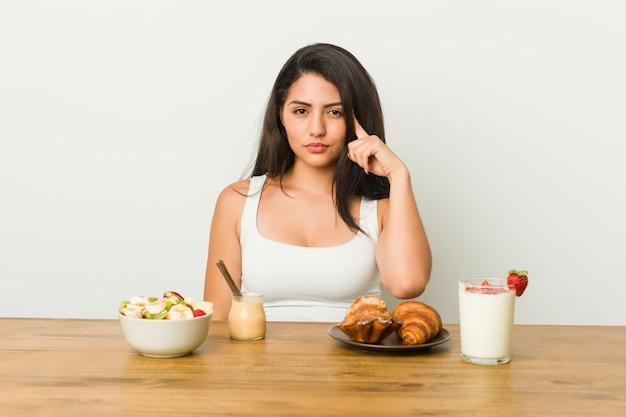 Giovane donna curvy che prende una prima colazione che indica tempio con il dito, pensando, concentrato su un compito