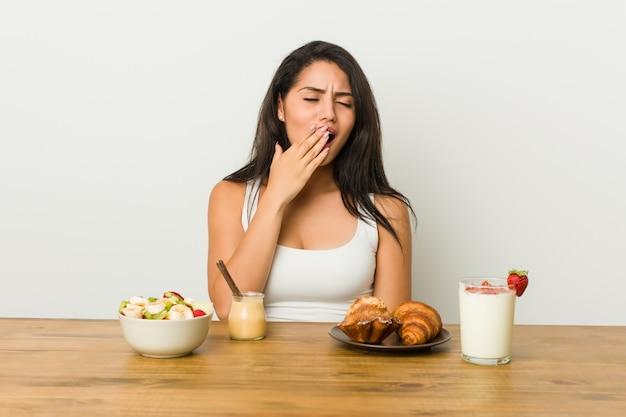 Giovane donna curvy che prende una prima colazione che sbadiglia mostrando un gesto stanco che copre la bocca di mano.