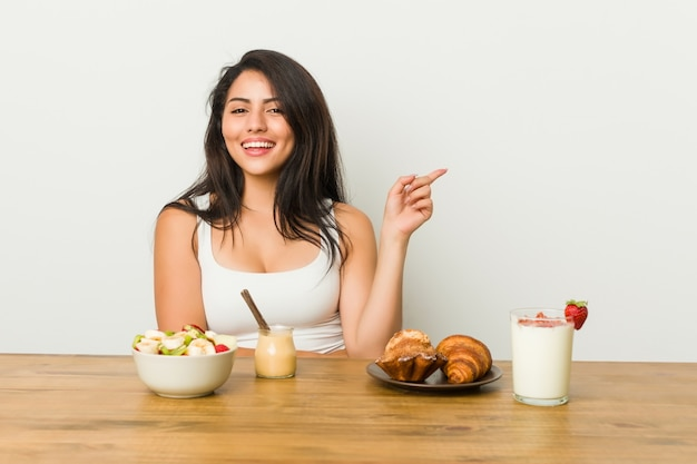 Giovane donna curvy che prende una prima colazione che sorride allegramente indicando con l'indice via.