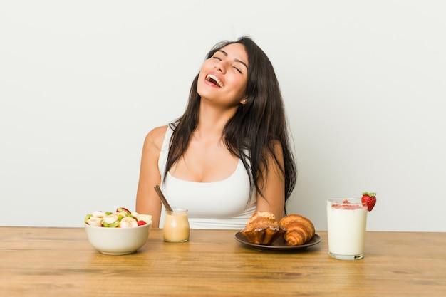 Giovane donna curvy che prende una prima colazione rilassata e felice che ride, collo allungato mostrando i denti.