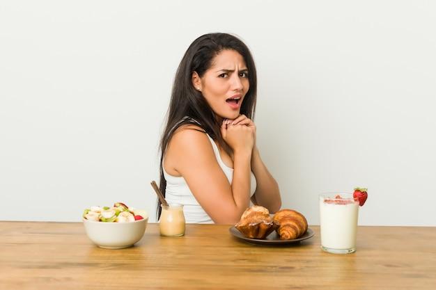 Giovane donna curvy che prende una prima colazione spaventata e impaurita.