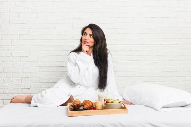 Giovane donna curvy che prende una prima colazione sul letto che guarda lateralmente con espressione dubbiosa e scettica.