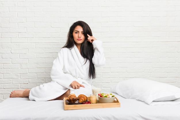 Giovane donna curvy che prende una prima colazione sul letto che indica tempio con il dito, pensando, concentrato su un compito.