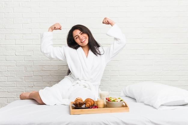 Giovane donna curvy che prende una prima colazione sul letto che mostra gesto di forza con le armi, simbolo di potere femminile