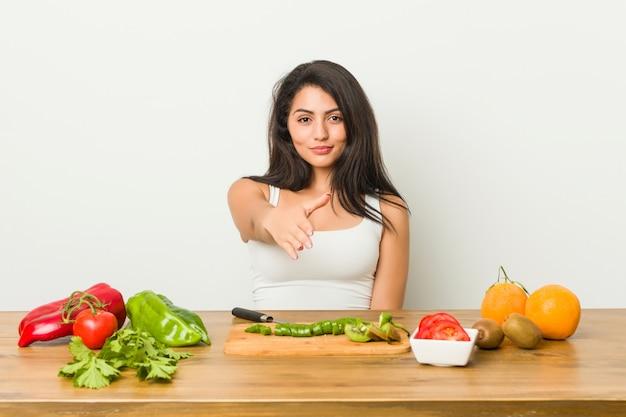 Giovane donna curvy che prepara un pasto sano che allunga mano alla macchina fotografica nel gesto di saluto