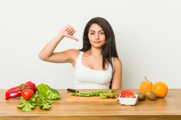 Giovane donna curvy che prepara un pasto sano che mostra un gesto di avversione, pollici giù