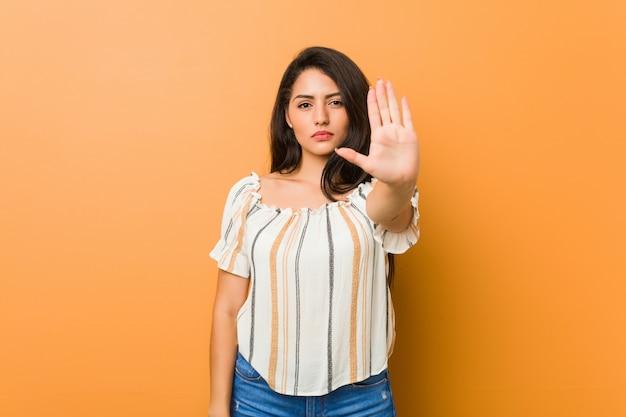Giovane donna curvy che sta con il fanale di arresto di rappresentazione della mano tesa, impedendovi.