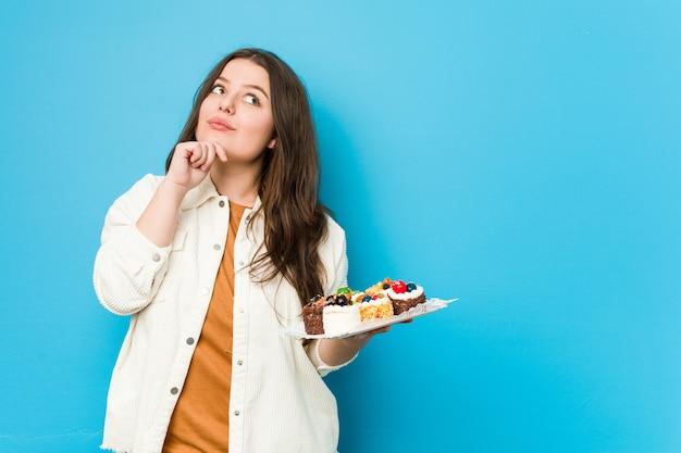 Giovane donna curvy che tiene le torte dolci che guardano lateralmente con l'espressione dubbiosa e scettica.