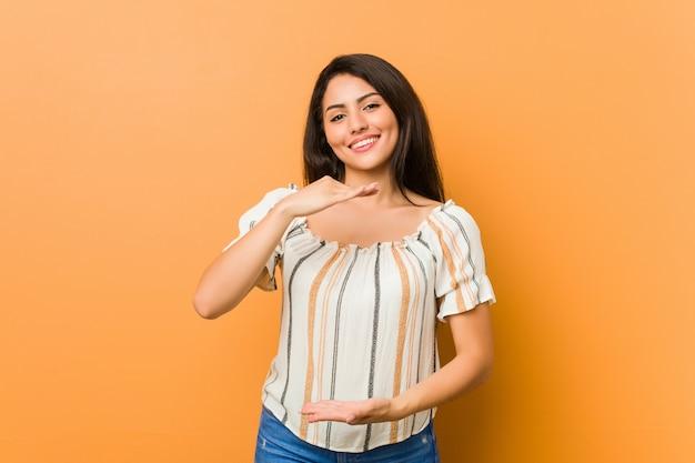 Giovane donna curvy che tiene qualcosa con entrambe le mani, presentazione del prodotto.