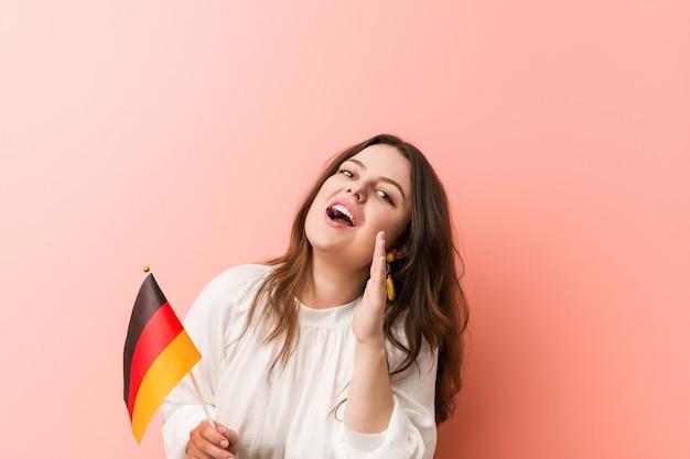Giovane donna curvy che tiene un gridare della bandiera della germania eccitato alla parte anteriore