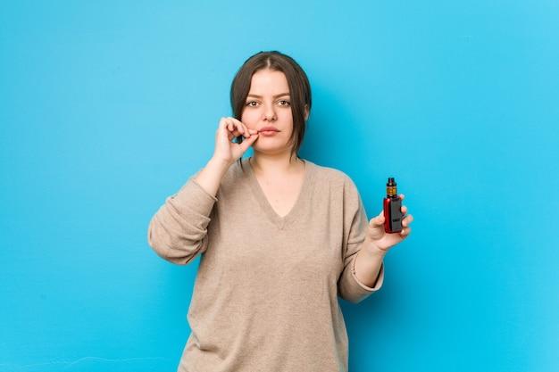 Giovane donna curvy che tiene un vaporizzatore con le dita sulle labbra mantenendo un segreto.