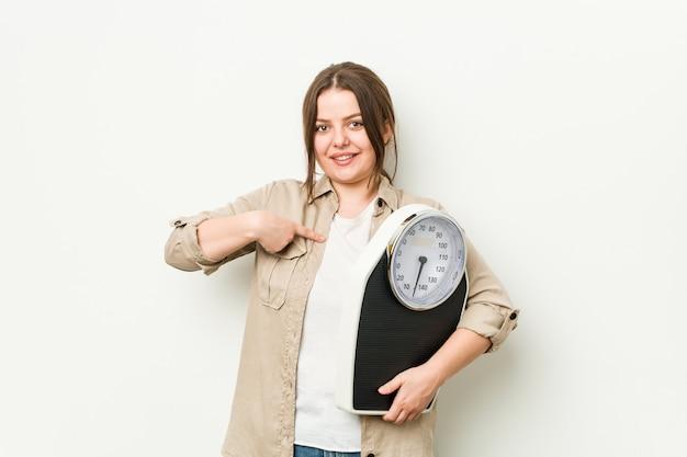 Giovane donna curvy che tiene una persona in scala che indica a mano uno spazio della copia della camicia, fiero e sicuro
