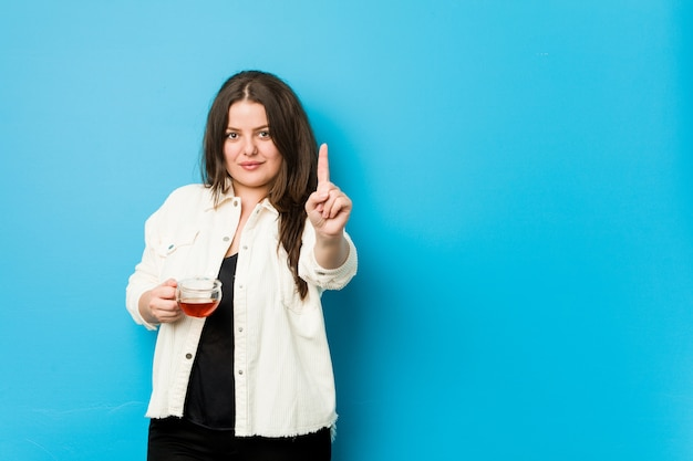 Giovane donna curvy che tiene una tazza di tè che mostra numero uno con il dito.