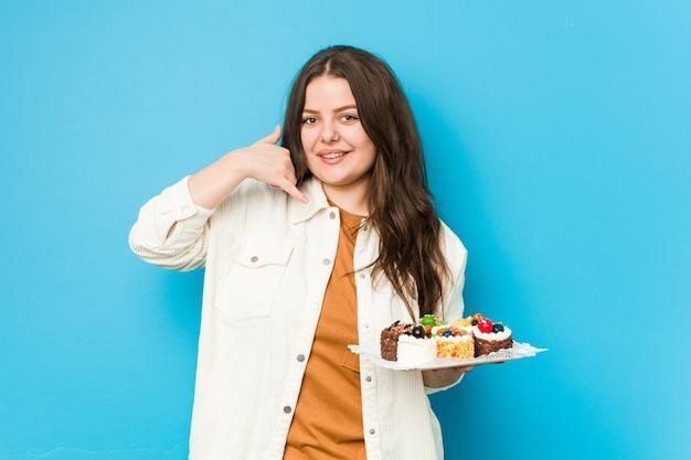 Giovane donna curvy che tiene una torte dolci che mostrano un gesto di chiamata di cellulare con le dita.
