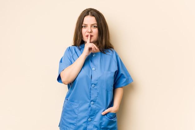 Giovane donna curvy dell'infermiera che mantiene un segreto o che chiede il silenzio.