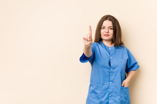 Giovane donna curvy dell'infermiera che mostra numero uno con la barretta.