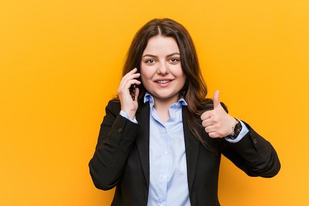 Giovane donna curvy plus size business in possesso di un telefono sorridente e alzando il pollice in su