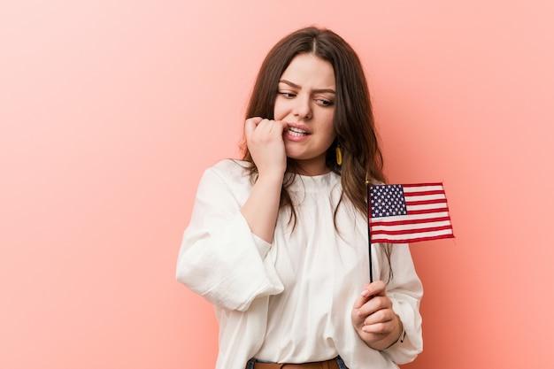 Giovane donna curvy plus size in possesso di una bandiera degli stati uniti mangiarsi le unghie, nervoso e molto ansioso.