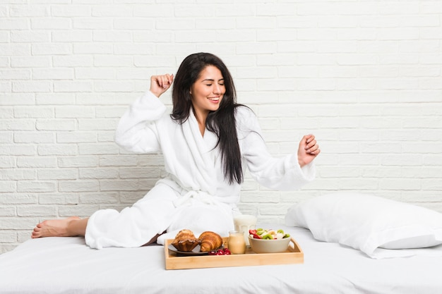 Giovane donna curvy prendendo una colazione sul letto ballando e divertendosi