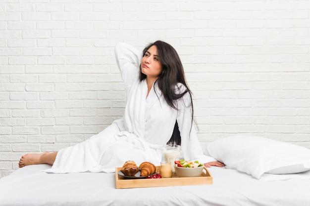 Giovane donna curvy prendendo una colazione sul letto toccando la parte posteriore della testa, pensando e facendo una scelta.