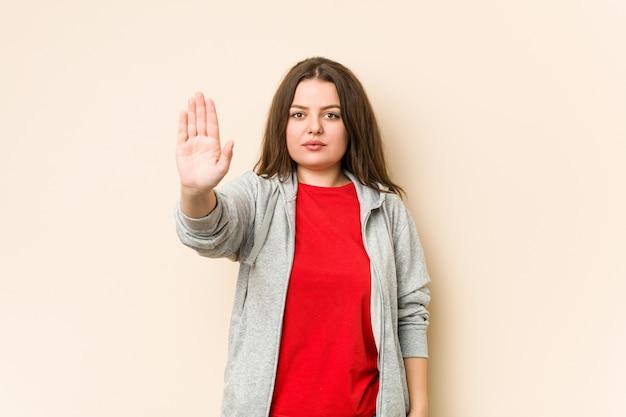 Giovane donna curvy sportiva che sta con il fanale di arresto di rappresentazione della mano tesa, impedendovi.