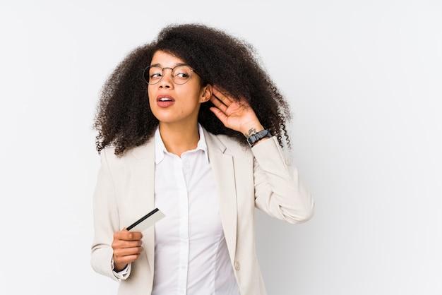 Giovane donna d'affari afro in possesso di un auto di credito isolato giovane donna d'affari afro in possesso di un credito di ascolto di un pettegolezzo.