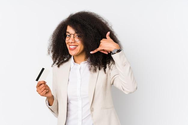 Giovane donna d'affari afro in possesso di un credito auto isolata giovane donna d'affari afro in possesso di un credito carshowing un gesto di chiamata di telefonia mobile con le dita.
