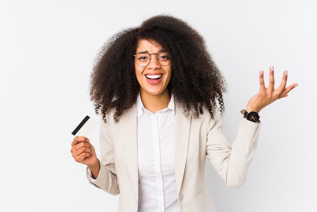 Giovane donna d'affari afro in possesso di un credito auto isolata giovane donna d'affari afro in possesso di un credito che riceve una piacevole sorpresa, eccitato e alzando le mani.