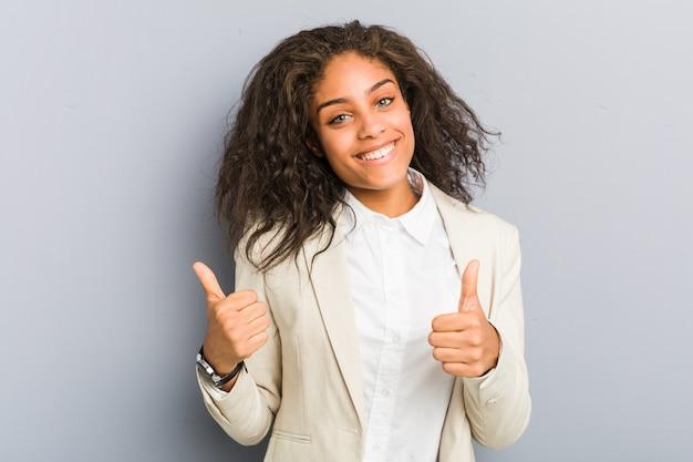 Giovane donna d'affari afroamericana alzando entrambi i pollici in su, sorridente e fiducioso.
