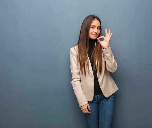 Giovane donna d'affari allegro e fiducioso facendo il gesto ok