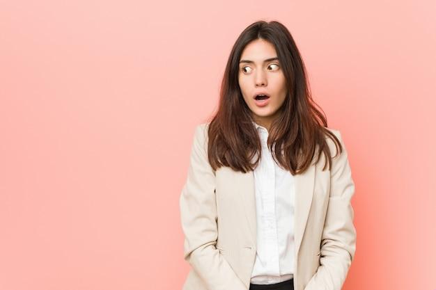 Giovane donna d'affari bruna contro un essere rosa scioccato perché qualcosa che ha visto.
