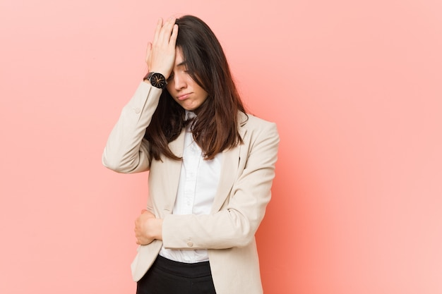 Giovane donna d'affari bruna contro un muro rosa dimenticando qualcosa, schiaffeggiando la fronte con il palmo e chiudendo gli occhi.